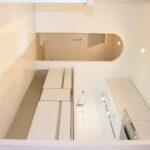 キッチン横にはパントリーへ続くアーチ型入口  キッチンの床にはお客様こだわりの「塩ビタイル」を施工